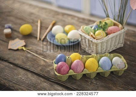 Close Up Of Dozen Of Tinted Eggs And Painting Set Standing On The Table. Focus On Colored Shell