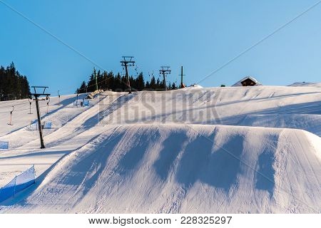 Beautiful View Of The Winter Ski Slope With A Lot Of Snow And Ski Lift On Side. Nice Blue Sky With N