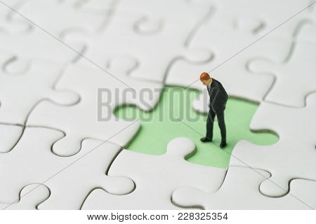 Finding The Missing Piece For Business Success Concept, Miniature People Businessman Standing And Lo