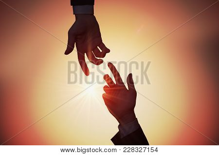 Help And Assistance Concept. Two Hands Are Reaching Each Other A