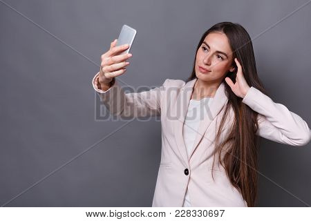 Young Brunette Business Woman Shooting Selfie Photo On Smartphone Over Gray Background Studio Backgr