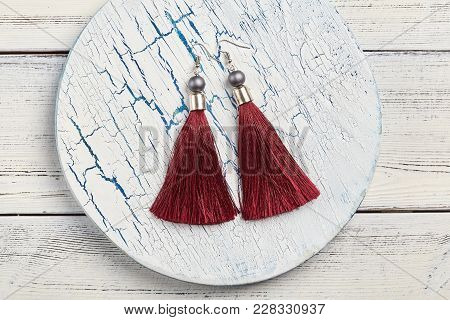 Red Tassel Earrings On White Background, Copy Space
