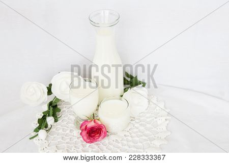 Horizontal Image Of A Tall Glass Jug Filled With Milk Along With Smaller Glasses Of Milk On White Ba