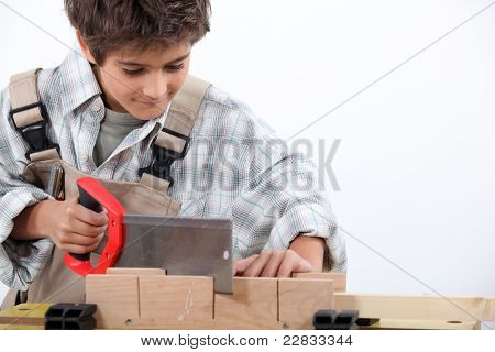 Young boy dressed as a carpenter sawing wood