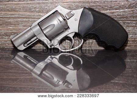 A Stainless Steel .357 Magnum Revolver On A Reflective Surface With A Wooden Background