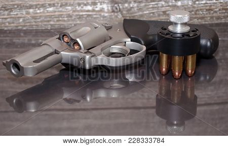 A Loaded, Stainless Steel .357 Magnum Revolver With A Black And Silver Loaded Speed Loader Next To I