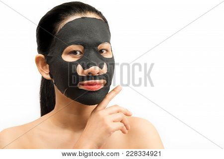Young Woman Doing Facial Black Mask Sheet With Purifying Mask On Her Face On White Background