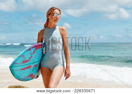 Portrait Of Slim Woman In Blue Bathing Suit And Trendy Sunglasses Enjoys Sunny Day On Ocean Beach, L