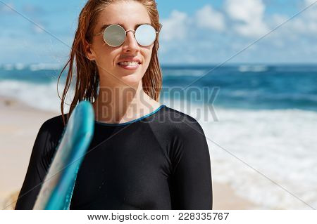 Photo Of Delighted Smiling Sporty Female In Shades, Wears Black Top And Trendy Shades, Has Wet Hair