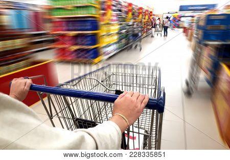 Women Pushing Trolley Cart In Supermarket Aisle