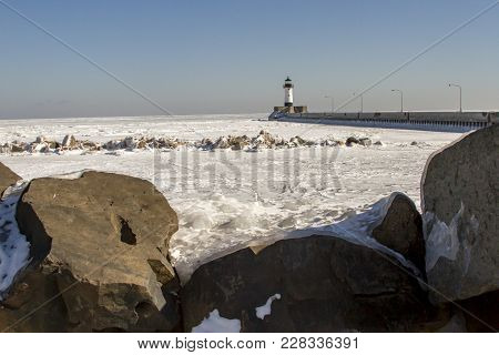 Lighthouse  On Frozen Rocky Shores Of Lake Superior Waterfront, Duluth, Minnesota In Winter