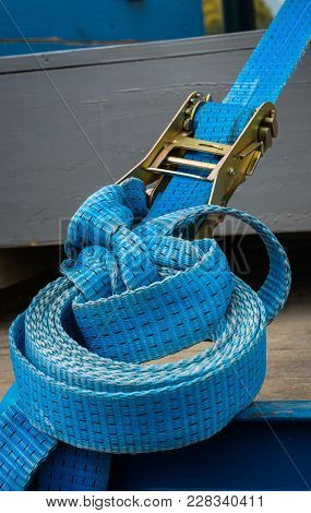 Blue Strap And Ratchet On A Truck Deck.