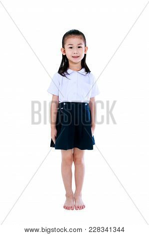Young Preschool Child In Uniform Smiling, A Look Of Enjoyment On Face. Full Body Of Cute Asian Girl