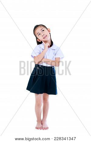 Full Body Of Preschool Girl In Uniform Smiling And Looking Up, Her Index Finger At Cheek. Cute Asian