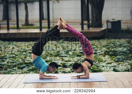 Young Asian Couple Performing Difficult Acroyoga Exercise