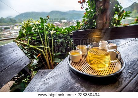 Tea In Glass With Tea Jug Set On The Wooden Table With Garden View, Traveling In Thailand