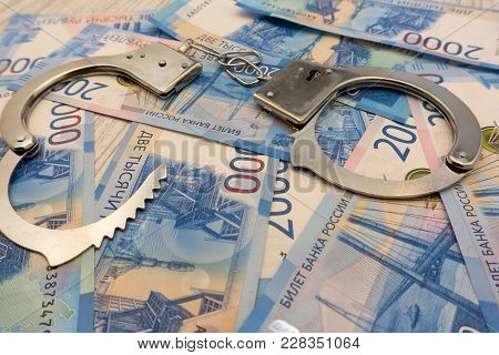 A Pair Of Handcuffs Close To The New Stack Of Banknotes For 2000 Rubles. Background Table Tree
