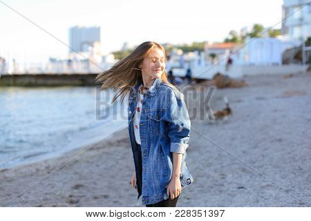 Pretty Girl  Enjoying Sea Air, Stands On Seashore On Sunny Day.