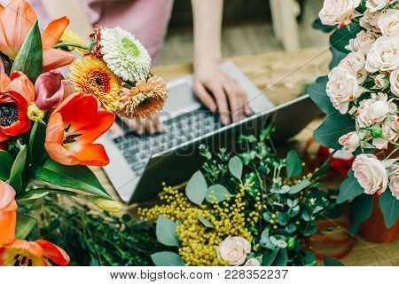 Faceless Shot Of Salesperson Using Laptop At Counter In Shop Surrounded With Flowers.