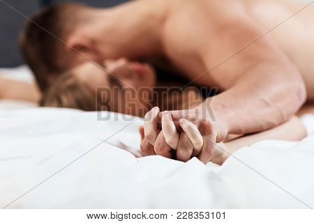 Young Lovers Kissing On Bed. Focused On Hands Of Couple Having Sex.