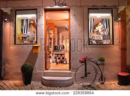 Rovinj, Istria, Croatia - June 21, 2017: Shop Front At Night With Lights And Old Bicycle  In Rovinj