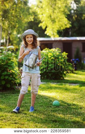 vertical portrait of happy child girl in gardener hat playing with watering can in sunny summer gard