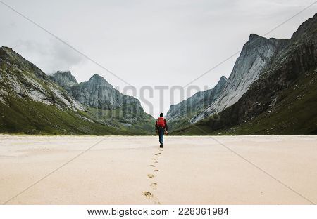 Man With Backpack Walking Away Alone At Sandy Beach In Mountains Travel Lifestyle Concept Adventure