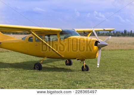 Small And Light Yellow Piper Aircraft Near To The Runaway  Ready To Take Off.