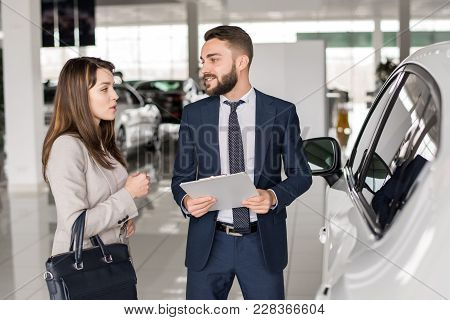 Portrait Of Handsome Car Salesman Talking To Young Woman Helping Her Choose Luxury Car  In Showroom