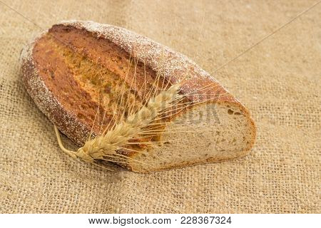 Partly Cut Oval Loaf Of The Wheat And Rye Sprouted Bread With Added Whole Sprouted Wheat Grains, Rye