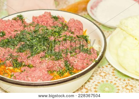 Fragment Of The Big Enameled Metal Bowl With Ground Meat On A Sauteed Onions And Carrots And Sprinkl