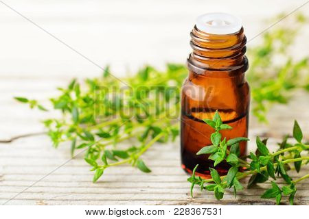 Thyme Essential Oil And Fresh Thyme On The Wooden Board