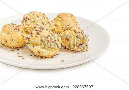 Fragment Of White Dish With Savory Profiterole Filled With Cheese And Sprinkled With Flax Seeds And