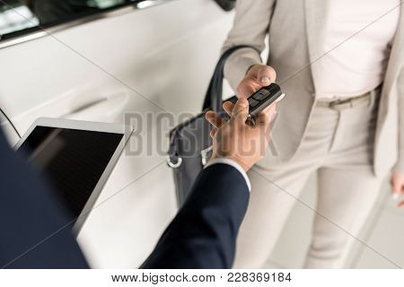 High Angle Close Up Of Car Salesman Giving Keys To Client Standing Next To White Luxury Car, Copy Sp