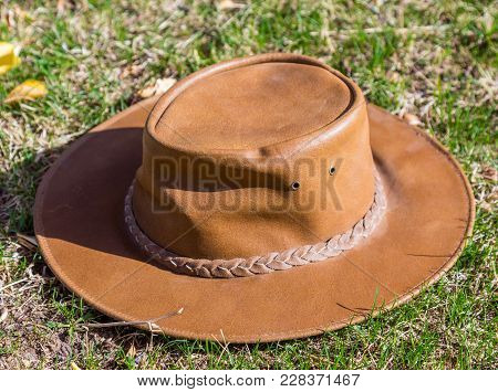 A Brown Cowboy Hat Rests On Fresh Grass In Sunny Weather.