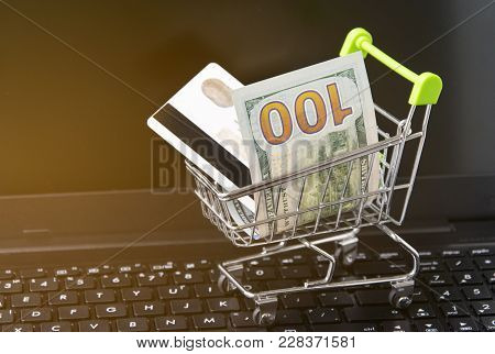 A Small Shopping Trolley With Money And A Card On A Laptop Background. An Online Shopping Concept