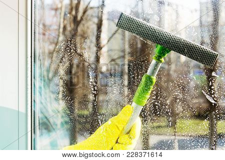 Cleaning Windows In The Spring With A Special Scraper. Spring Cleaning
