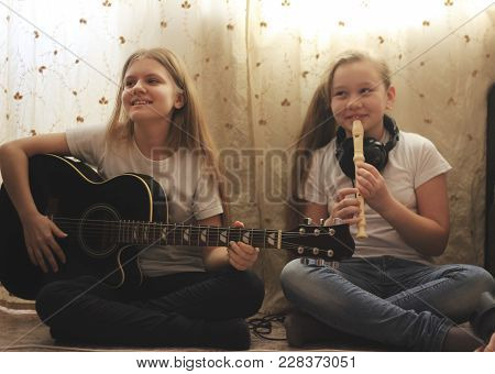 Two Female Teens Playing Musical Instruments Sitting On The Floor At Home, Youth Hobby And Leisure C