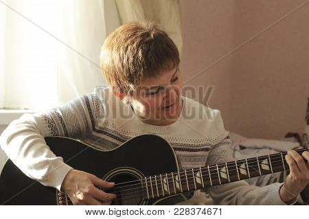 Middle-aged Woman Playing Guitar At Home, Hobby And Leisure Concept