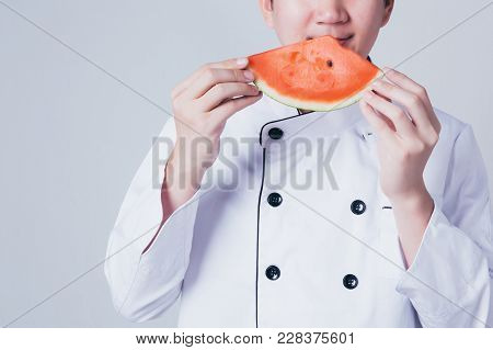 Young Chef Smelling And Sniffing Freshness Of Newly Sliced Water Melon