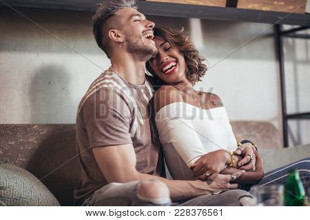 Two Happy Mixed Race Couple Having Fun At The Coffee Shop. Couple Enjoying At A Coffee Shop, Sitting