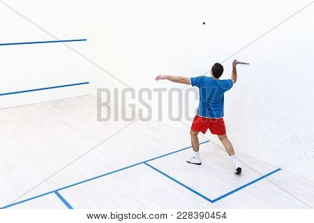 Back View Of Squash Player Hitting A Ball In A Squash Court. Squash Player In Action. Man Playing Ma