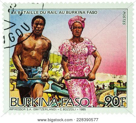 Moscow, Russia - February 24, 2018: A Stamp Printed In Burkina Faso, Shows African Man And Woman Car