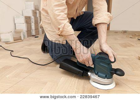 worker  polishes oak parquet