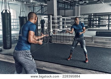 On The Way To Success. Handsome Young African Man In Sport Clothing Exercising Using Balls While Sta