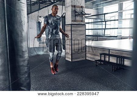 Pushing Hard To Win. Full Length Of Young African Man In Sport Clothing Skipping Rope While Exercisi