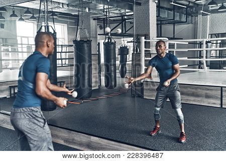Another Way Of Training. Handsome Young African Man In Sport Clothing Exercising Using Balls While S
