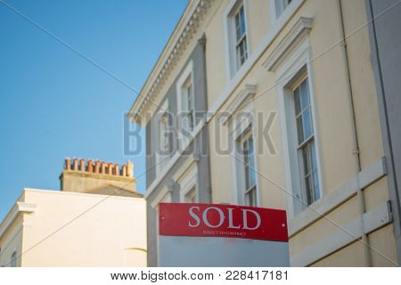 Sold Sign With Victorian Houses In The Background