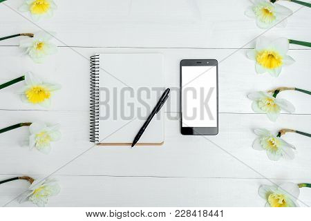 Frame Of Yellow Narcissus On White Wooden Background. Blank Card Flat Lay. Top View On Table With Na