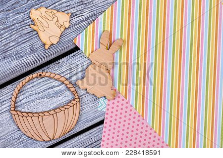 Easter Plywood Figurines On Wooden Background. Cut Out Wooden Figures Of Easter Rabbits And Basket O